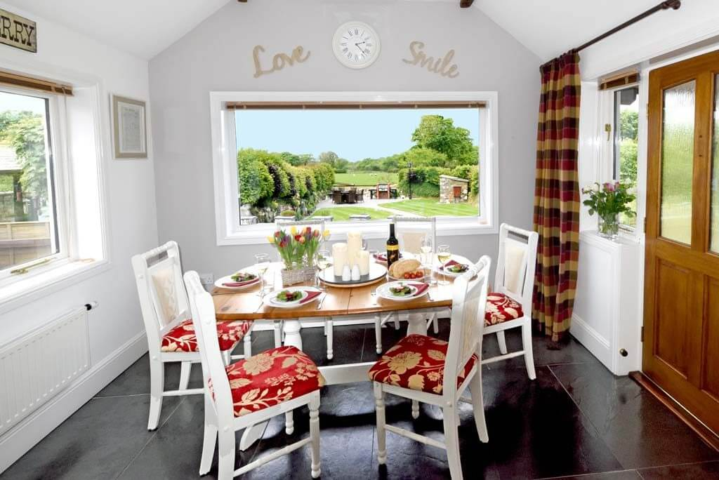 Dining room overlooking garden and meadow beyond at our luxury cottage Cornwall