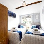 Large twin beds with views over the garden in our luxury cottage Cornwall